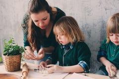 Мать варя с детьми в кухне Отпрыски малыша печь совместно и играя с печеньем дома Стоковое Изображение RF