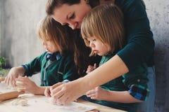 Мать варя с детьми в кухне Отпрыски малыша печь совместно и играя с печеньем дома Стоковые Изображения