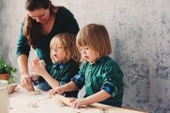 Мать варя с детьми в кухне Отпрыски малыша печь совместно и играя с печеньем дома Стоковое Фото