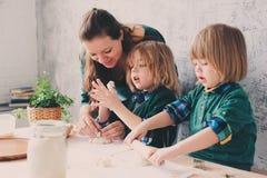 Мать варя с детьми в кухне Отпрыски малыша печь совместно и играя с печеньем дома Стоковое фото RF