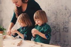 Мать варя с детьми в кухне Отпрыски малыша печь совместно и играя с печеньем дома Стоковые Изображения RF
