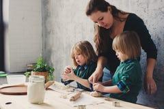 Мать варя с детьми в кухне Отпрыски малыша печь совместно и играя с печеньем дома Стоковые Фото