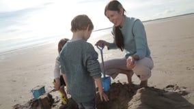 Мать выкапывая с детьми на пляже сток-видео