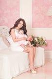 Мать в белом платье сидя с младенцем на софе Стоковое Фото