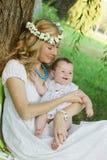 Мать в венке держа усмехаясь ребёнок Стоковые Изображения