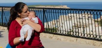 Мать в красной футболке держа один ребенка месяца старый newborn стоковая фотография rf