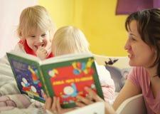 Мать говорит сказ в кровати к ее детям Стоковая Фотография