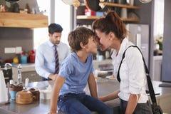 Мать говоря до свидания к сыну по мере того как она выходит для работы стоковые изображения