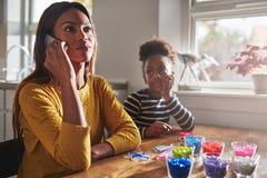 Мать говоря на телефоне забывая ребенка Стоковые Изображения RF