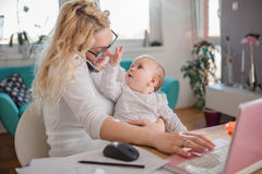 Мать говоря на умном офисе телефона дома Стоковые Фото