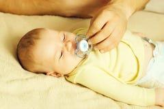Мать дает pacifier младенца s стоковая фотография rf