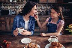 Мать девушки подавая с печеньем стоковые изображения