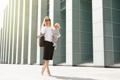 Мать дела в городе с младенцем в ее руках Стоковые Изображения RF