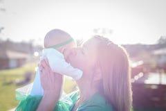 Мать держа младенца вверх в ярком солнечном свете стоковые фотографии rf