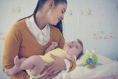Мать держа младенца и подготавливая на спать стоковая фотография