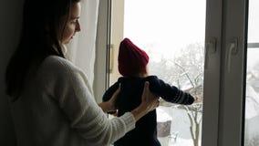 Мать держа молодого сына на окне сток-видео