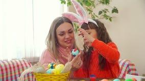 Мать держит голубое яйцо цыпленка, и моя дочь предусматриванная в краске с вашими пальцами выходит трассировки она носит зайчика сток-видео