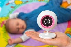 Мать держит камеру монитора младенца для безопасности ее младенца Стоковые Изображения RF