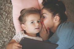 мать дочи домашняя Мать прошептанная к ее дочери дальше Стоковые Изображения