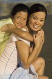 Мать девушки обнимая на пляже Стоковое Изображение