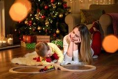 Мать ее сын любознательно играя с поездом игрушки стоковое изображение