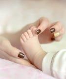 Мать держа палец ноги младенца Стоковые Фотографии RF
