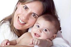 Мать держа усмехаться младенца Стоковые Изображения