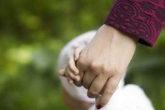 Мать держит руку ребенка Стоковое Фото