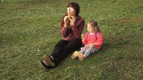 Мать ест гамбургер, дочь ест клубники сидя на лужайке сток-видео