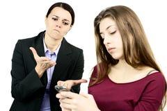 Мать дела сердитая с дочерью пристрастившийся к сотовому телефону Стоковое фото RF