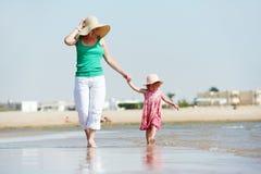 Женщина и маленький ребенок гуляя на море пляж Стоковая Фотография RF