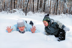 Мать зимы с ее сыном потакает лож на снеге в лесе Стоковое Изображение RF
