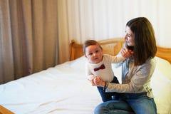Мать играя с ее младенцем в спальне E стоковая фотография rf