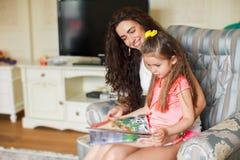 мать игры дочи компьютера книги ослабляя совместно Стоковые Изображения RF