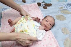 Мать изменяя пеленку стоковое фото