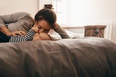Мать изнеживая ее младенца стоковые фотографии rf