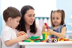 Мать или учитель с игрушками строительного блока детей дома или амбулаторным учреждением Дети играя с блоками цвета воспитательно стоковые изображения