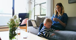 Мать используя компьтер-книжку пока позаботить о ее сын 4k видеоматериал