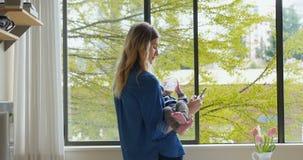 Мать используя мобильный телефон пока подающ ей младенец 4k сток-видео