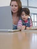 Мать используя компьтер-книжку пока расцветка дочери на таблице Стоковые Изображения