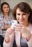 Мать используя мобильный телефон с разочарованным дочь-подростком Стоковые Изображения RF