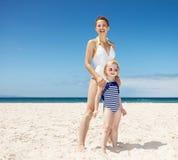 Мать и девушка в купальниках на песчаном пляже на солнечный день Стоковое Изображение