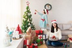 Мать и девушка украшают рождественскую елку Стоковые Изображения
