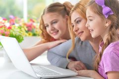 Мать и девушки сидя на таблице и используя компьтер-книжку Стоковая Фотография