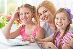 Мать и девушки сидя на таблице и используя компьтер-книжку Стоковые Изображения RF