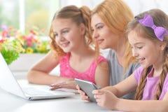 Мать и девушки сидя на таблице и используя компьтер-книжку Стоковое Изображение RF