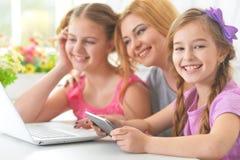 Мать и девушки сидя на таблице и используя компьтер-книжку Стоковые Изображения