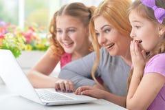 Мать и девушки сидя на таблице и используя компьтер-книжку Стоковое фото RF