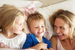Мать и дети ослабляя совместно в кровати Стоковые Изображения RF