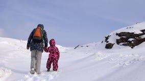 Мать и дочь взбираются вверх холм на снежном пути на холодный зимний день сток-видео